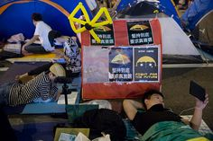 Umbrella Revolution Hong Kong, Demonstrators sit near tents outside the Central Government Offices in the Admiralty business district of Hong Kong, China, on Saturday, Oct. 11, 2014. Pro-democracy protesters rallied for a second night in Hong Kong to maintain pressure on the government after it scrapped planned talks with student leaders. Photographer: Brent Lewin/Bloomberg via Getty Images