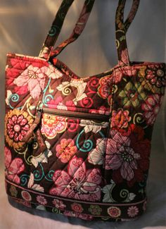 Known for its hand-stitched craftsmanship, Vera Bradley broke the mold with the companys bright, patterned bags. This particular handbag is large enough to use as an everyday purse. It is quilted in the classic Vera Bradley style and features the Mod Floral pattern in pink (retired). There is a small zippered pocket on the outside of the bag as well as one on the inside. The other interior side has three pockets sewn into it - perfect for sunglasses, cell phones, etc. Its a spacious bag that…