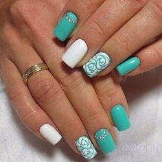 Pretty green and white rose nail art design. The roses are painted in white against the sea green background. The other nails are painted in all white and it helps make the nails pop out of the design.