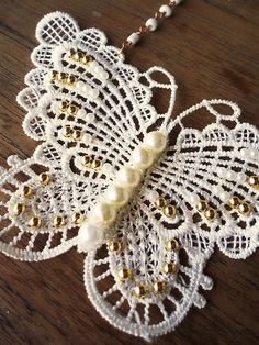 butterfly lace with pearls.  This is machine lace, but I would love to see something like this in real needle lace