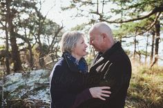 Happy older middle aged couple (fifties)  looking at each other smiling outside in winter by robcampbell   Stocksy United