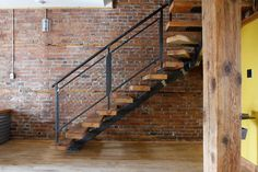 Handsome-Black-Metal-home-designing-tips-Montreal-Industrial-brick-walls-exposed-brick-industrial-loft-natural-wood-trim-open-risers-rustic-single-stringer- ...