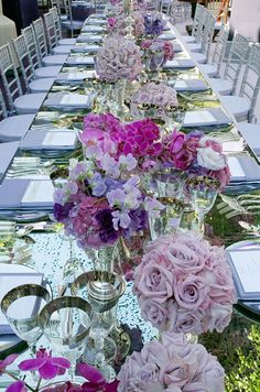A long mirrored table reflects arrangements of purple roses, pink orchids and pink and purple hydrangeas.