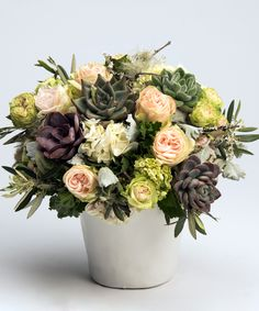 Succulent & Rose Garden This unique collection of roses and hydrangea is accented with succulents and designed in a white ceramic container for a one-of-a-kind arrangement.