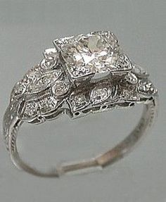 I LOVE THIS RING ❤ Platinum Art Deco Filigree Engagement Ring Set in platinum, this spectacular 1920's engagement ring holds a round old European cut diamond that weighs 1.20 ct. The color of the diamond is a very white G and the clarity a very clean VVS. The incomparable setting is an impressive web of filigree. Around the center stone is a crown like wreath of 10 round smaller diamonds contoured by 2 side marquis diamonds that add the finishing touch. A hypnotic and spellbinding creation.