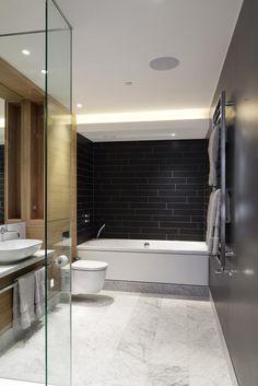 Das Bad ist überschwemmt kontrastreich, taktile Elemente, mit schwarzen Fliesen Wände, reichen natürlichen Holz-Mobiliar, Marmorboden und einem schwimmenden Waschtisch mit Schiff Spüle.