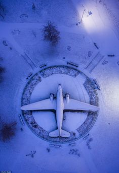 Best Aerial Drone photography from around the world - WWII airplane by Salim Madjd A World War 2 airplane at the outdoor display of the Belarusian Great Patriotic War Museum is caked in snow from a light snowstorm overnight, with a photo taken during 'blue hour' in the early morning. Skypixel Drone Photo Competition Drone Magazine Australia News #Drone