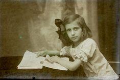Dziewczynka przegląda Głos Poranny.Przy stoliku siedzi dziewczynka zwrócona profilem w lewo.Lewą rękę trzyma na stole, przytrzymując gazetę. Prawą delikatnie ją podnosi.Widzimy tytuł artykułu -CO NIESIE MODA. Widać po szacie graficznej,że to zapewne #GłosPoranny,który zawsze w okresie międzywojennym poświęcał modzie całą stronę #Bielski #Fotografia #zdjęcia #moda #historia #płytkiszklane  #fotobielski