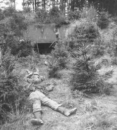 Two German KIAs lie outside a well camouflaged bunker somewhere in France. The bunker was knocked out by troops of the US 22nd Infantry Division on Sept 15, 1944.