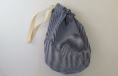 This handy navy blue and white drawstring bag with candy stripes is ideal as an easter basket or childrens party bag. The navy blue and white striped