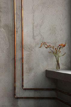 las tuberías de cobre a la vista pueden resultar muy decorativas, su color contrasta con el gris de la pared de cemento