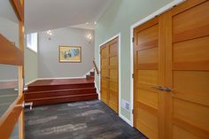 Natural finished closet doors with white trim.