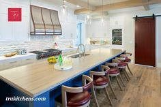 One goal of this lakehouse design was to provide ample storage space so that all the day-to-day items can be put away out of sight. In the kitchen, paneled appliances create a streamlined look. Along the refrigerator wall, floor-to-ceiling inset cabinets painted Glacier white on maple open to reveal many compartments. The Kensington Blue painted kitchen island, a nod to nautical style, offers ample area for food prep and in-kitchen seating. Nautical Style, Nautical Fashion, Painted Kitchen Island, Inset Cabinets, Kitchen Seating, Transitional Kitchen, Food Prep, Painting Cabinets, Refrigerator