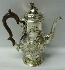 George II Silver Coffee Pot  An exceptional quality antique sterling silver coffee pot of baluster shape on pedestal foot. Very beautifully decorated with crisply chased scrolls, flowers, leaves and hatching. On top there is a pretty cast flower finial. . London 1742. Maker Louis Dupont
