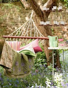 rope hammock with green and pink quilt and pillows, jadite pitcher and glasses, hanging votives
