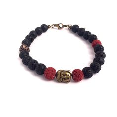 """Bali Lava Bracelet. The powerful yet playful 'Bali' men's fashion bracelet exudes strength and masculinity. Handcrafted in our studio, inspired by Apache warrior tribes, this stylish bracelet, measuring approximately 9"""", features black and red lava rock stones and a singular copper bead. The bracelet is finished off with an antique bronze Buddha centrepiece, lobster clasp and Native American Indian feather charm."""