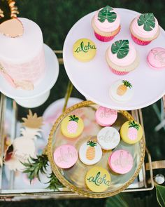 "Cupcakes and macarons from Sweet & Saucy Shop were decked out with edible palm leafs, ""Aloha"" messages, or painted pineapples. Copy this look when creating a similar dessert bar, or ask your baker to incorporate these elements on your wedding cake."
