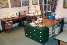 The U shape sewing room - very nice layout.  Cutting table is along the wall on the right.  I wonder if she can use the table behind the green storage cabinet as a quick cutting table too.  Green storage cabinet perfect size for storing fat quarters.
