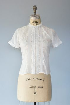 Beautiful 1950s lightweight white cotton blouse with lace trim and embroidered details. Buttons up the back and has sweet little peter pan style