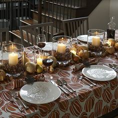 love the hurricanes on the table for Thanksgiving - filled with acorns like here or coffee beans (from another C&B pic)  London Wide Short Hurricane in Candleholders | Crate and Barrel