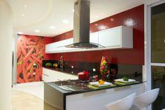 CASA NA SERRA DA CANTAREIRA. Na cozinha, de 39,08 m², da casa de campo projetada por Aquiles Nicolas Kilaris, o vermelho é destacado na imagem adesivada e nas pastilhas vermelhas (Colormix). A bancada é de granito preto são gabriel e os armários feitos de fórmica branca e vidro serigrafado.