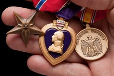Photo about Man Holding Purple Heart, Bronze and National Defense War Medals in The Palm of His Hand. Ranger School, War Medals, Hand Images, First Second, American Soldiers, Badass Women, Hold On, How To Apply, Bronze