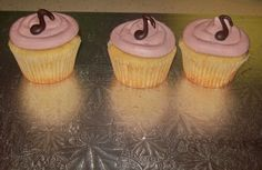 Cupcake trio.  Vanilla cake with raspberry filling and raspberry butter cream topped with chocolate note.