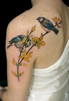 Cheery and colorful tattoo of birds on a branch. The flowers are also in bright colors complementing the color combination of the birds as well.