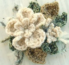 This corsage pin or brooch is made with a cream cashmere yarn with a fine metallic gold thread running through it. Also with shimmery glitter green and metallic gold for the leaves. Perfect for the upcoming holiday season to add some glitz to your wardrobe. Has felt on the back with a pinback. Measures 3 1/2 inches diameter.