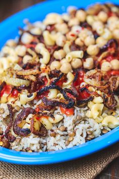 Egyptian Koshari Recipe   The Mediterranean Dish. Hands down a family favorite. A comforting bowl of spiced lentils and rice with chickpeas, tiny pasta, and tomato sauce. Topped with thin crispy onion rings. A tasty, budget friendly, vegan recipe! See it on TheMediterraneanDish.com