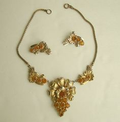 "This early 1900s Art Nouveau set has a three-piece ""bib"" necklace with antiqued gold flowers loaded with amber rhinestones, and matching clip-on earrings. The matching earrings have the clip mechanism"