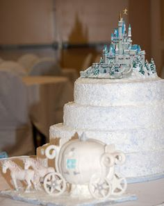 Large round four tier white Cinderella Castle Wedding Cake with castle in blue hues and Cinderella carriage at the base of the cake.