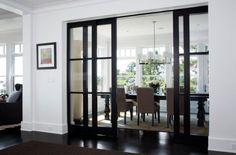 Elegant dining area concealed by sliding glass doors in wooden frame