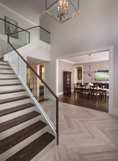 Foyer flooring ideas staircase transitional with dark wood staircase glass stair railing herringbone floor herringbone wood floor Modern Stair Railing, Stair Railing Design, Wood Railing, Staircase Railings, Modern Stairs, Railing Ideas, Banisters, Staircases, Tile Stairs