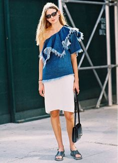 Stylish Victoria Sekrier wears a frayed denim one-shoulder top with a white midi skirt, sandals, and a flap bag