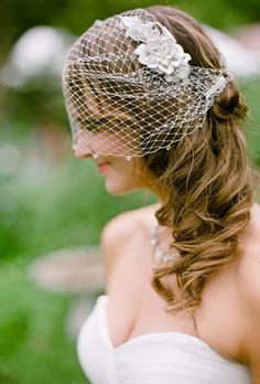 """Maxine's vintage-esque birdcage veil was adorned with silk flowers and pinned ever-so-slightly to the side of her soft curls.""- Brides"