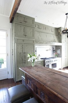 One of a kind kitchen with an iron candelabra chandelier hung from beadboard ceilings over ceiling height green cypress cabinets accented with nickel hardware, white marble counters and a solid marble backsplash.
