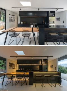 This modern black kitchen has a large island with a wood dining table at one end. Black accents like the chairs, table details and track lighting have also been included.