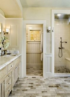 cottage style bathroom with stone floors, bead board walls, carrera marble countertop, and a little square window.