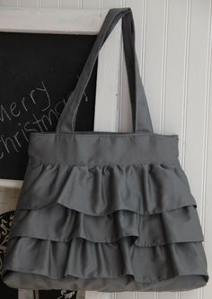 This Ruffle Bag is super cute, and super durable! The fabric is a gray bottomweight fabric. All the outside seams are top-stitched, and the handles and bottom are reinforced.
