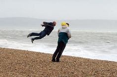 The great British weather! Two men enjoy the sea air In Dorset