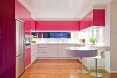 U-Shaped Pink and White Modern Kitchen with Pink Kitchen Cabinet and Round Dining Table