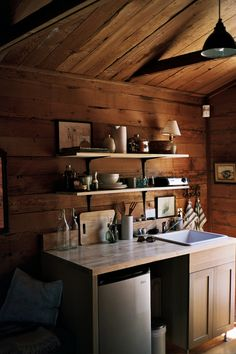 full butcher block countertop, fridge under half, cabinet on other half, floating shelves above, microwave on countertop