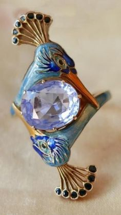 - Christie's Jewelry Geneva - René LALIQUE - An oval-cut Sapphire and Enamel Peacock ring.