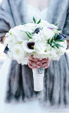 These winter wedding flowers are so elegant and romantic. With a pop of a plum shade of purple, white and the so-classy 'something old' portraits attached at the base of the bouquet this one is a favorite. The bride is wearing a vintage fur cover up to keep cozy.
