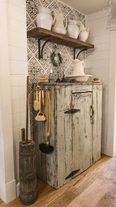 This narrow hallways sits across from a laundry room/closet. The farmhouse has very little storage making this jam cupboard valuable storage space. The stencilled wall and faux shiplap walls provide the perfect backdrop to the Ironstone treasures that are pretty to look at while folding laundry or scrubbing stains!