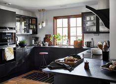 Det vita kaklet och den mörka bänkskivan bidrar båda till att framhäva de träfärgade fönsterkarmarna. Karmarna ger samtidigt en mjukhet till köket, som med sin strama färgsättning kunde ha blivit hårt utan dem och trägolvet.