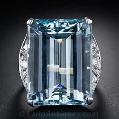 A glistening and sizable - 27 carats - emerald-cut aquamarine displaying a serene liquid pastel-blue hue is artfully presented in a sleek and streamlined 14 karat white gold mounting with sparkling diamond crescents enlivening the shoulders. A cool and refreshing cocktail ring, circa 1950s.