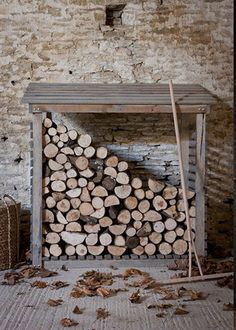 A wide wooden log store with slanted slatted roof. The piece is open at the front, pictured with an abundance of logs and a wooden rake to the side. Outdoor Firewood Rack, Firewood Shed, Firewood Storage, Storage Bins, Outdoor Storage, Stacking Firewood, Storage Ideas, Lavabo Exterior, Interiores Shabby Chic