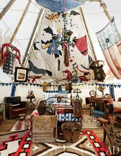 A remnant of an original chief's tepee hangs over the Victorian cast-iron bed, which is topped with antique bedding and Ralph Lauren Home shams; the chandelier is also Victorian.